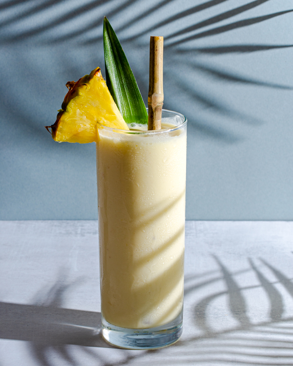 One glass of Pina Colada garnished with a pineapple spear and leaf, with a bamboo straw